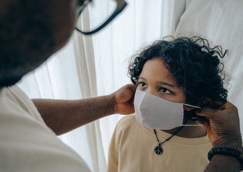 parent putting a mask on a child